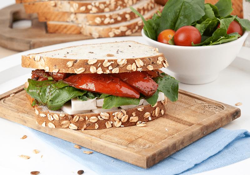 Sándwich Oroweat de pimientos y tomates asados con queso curado.